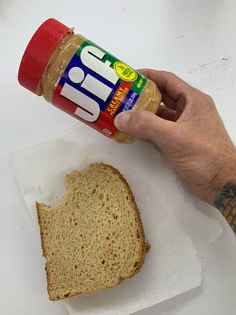 peanut butter and jelly sandwich and jar of JIF peanut butter